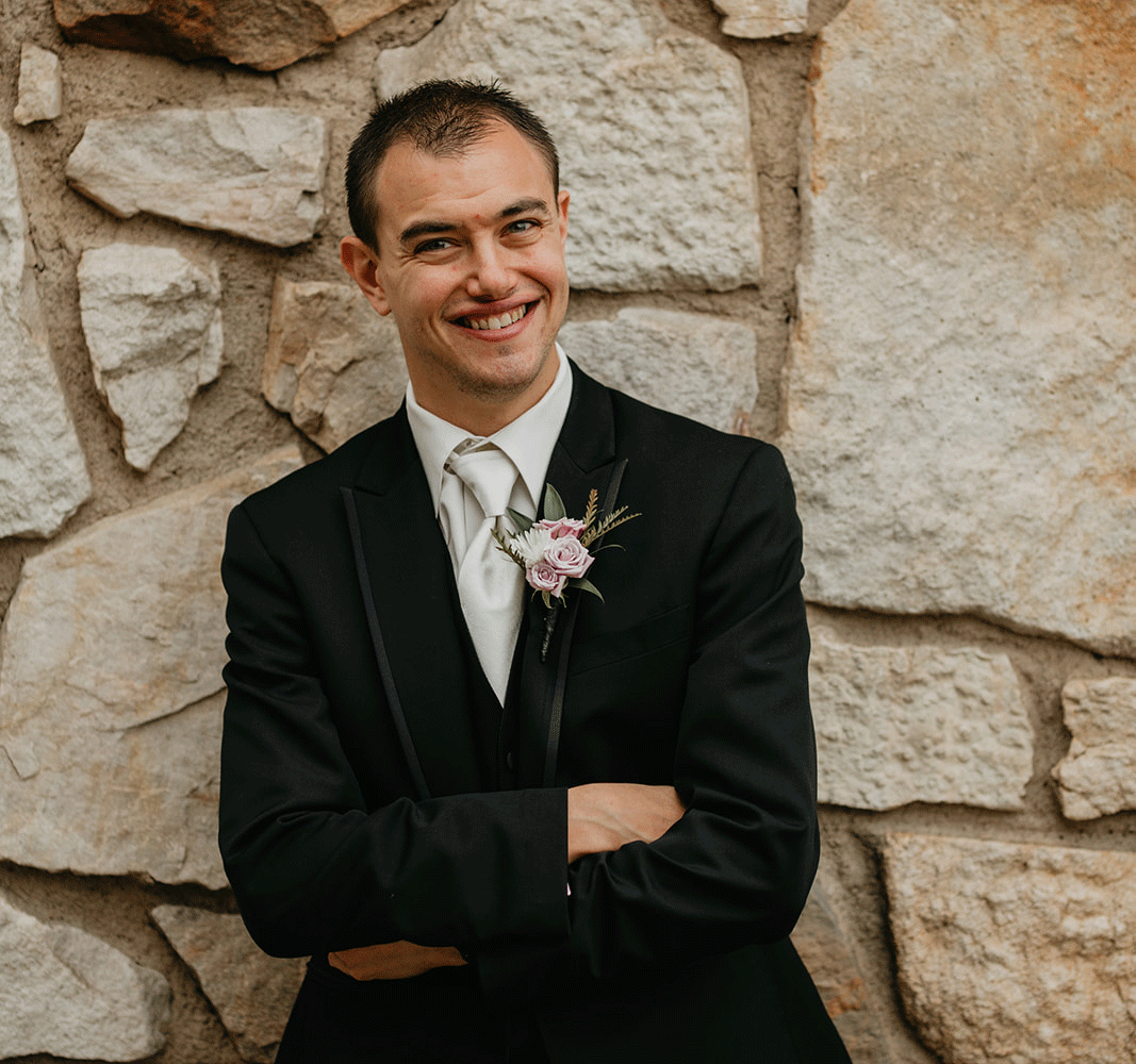 Eric Mayhue in a nice tux posing against a stone wall